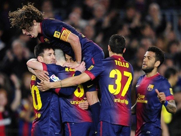 Lionel Messi (vlevo) slaví se spoluhráči v čele s Carlesem Puyolem (nahoře) gól v zápase s La Coruňou.