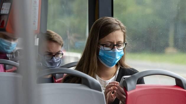 Cestující s nasazenou rouškou sedí 1. září 2020 v tramvaji v Praze. Tento den kvůli koronaviru začala platit povinnost nosit roušky v hromadné dopravě, na úřadech a ve zdravotnických a sociálních zařízeních