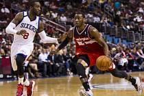 Basketbalista Washingotnu John Wall (v červeném) obehrává hráče Philadelphie Tonyho Wrotena.