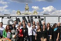 Kandidáti Pirátské strany pózují před volebním autobusem v Praze při zahájení kampaně do krajských a senátních voleb. Uprostřed v bílé košili je předseda strany Ivan Bartoš.