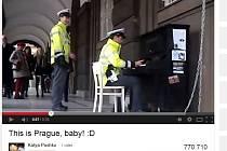 Pražský policista v uniformě krátce zahraje na klavír umístěný v centru u budovy filozofické fakulty.
