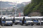 Policejní vozy a těžkooděnci dohlíží na pochod srbských fanoušků Prahou před bitvou se Spartou.