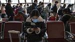 Cestující na vlakovém nádraží v Pekingu 29. března 2020