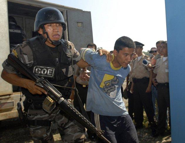 Ekvadorský policista eskortuje mladíka podezřelého ze sympatií ke kolumbijské gerile FARC.