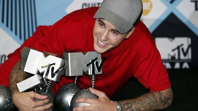 Kanadský popový zpěvák Justin Bieber pózuje s hudebními cenami MTV.