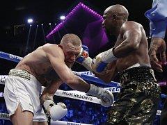Floyd Mayweather (vpravo) zasazuje tvrdý úder Conorovi McGregorovi.