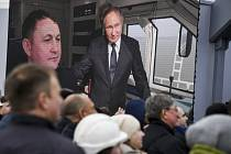 Lidé sledují na obří televizní obrazovce ruského prezidenta Vladimira Putina ve vlaku, který míří přes most spojující Rusko a Krymský poloostrov v Tamanu