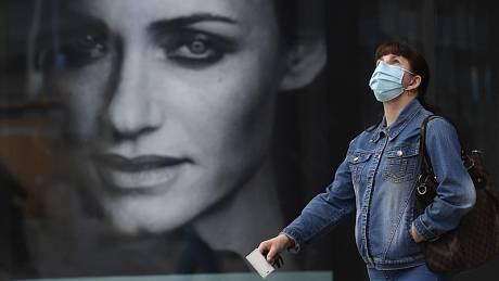 Žena v ochranné roušce proti koronaviru u obchodního centra.