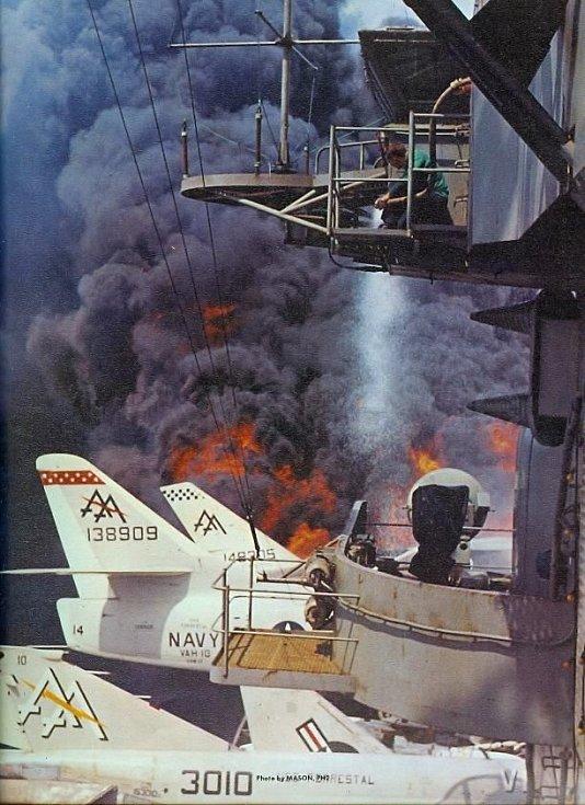 Další snímek ničivého požáru na palubě Forrestalu zachycuje i člena posádky držícího požární hadici