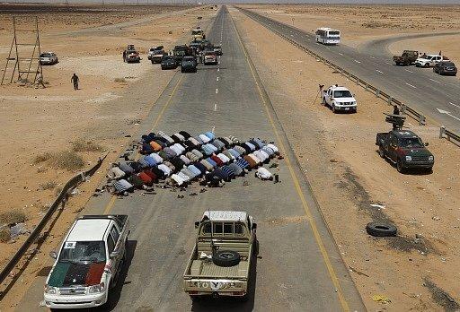 Bojovníci proti Kaddáfímu se modlí na kontrolním stanovišti  blízko města Abu Grein, asi 160 km na západ od Sirty, jedné z posledních bašt Kaddáfího. Libye,12. září 2011