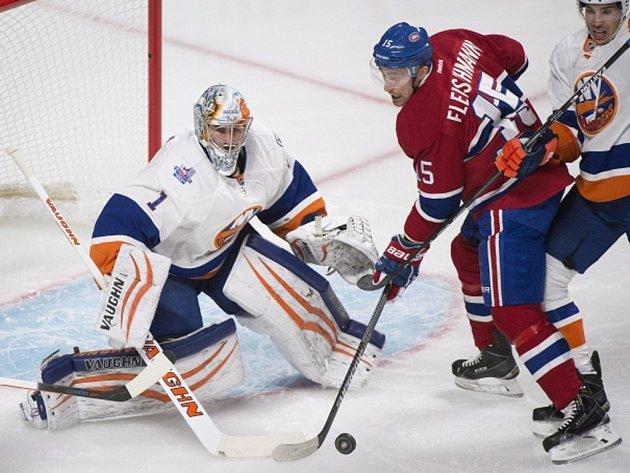 Tomáš Fleischmann z Montrealu se snaží překonat brankáře Islanders Thomase Greisse.