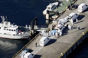 Zdravotníci v ochranných oblecích kontrolují cestující z výletní lodi Diamond Princess v přístavu v Jokohamě.