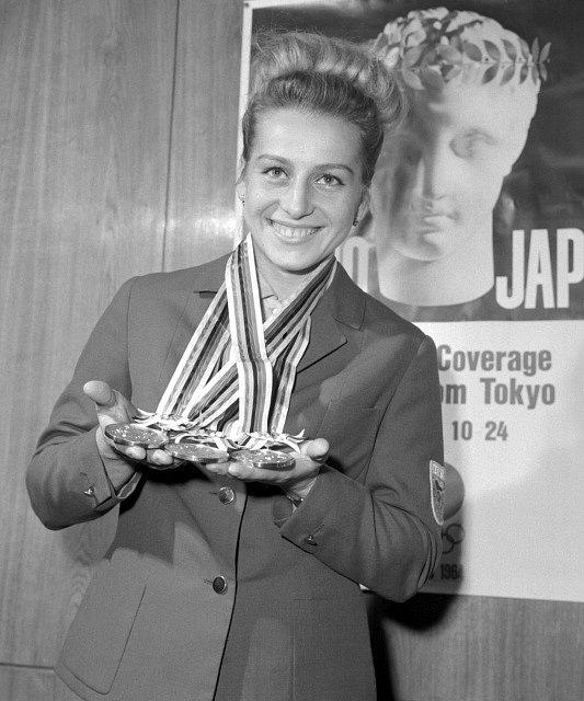 Portrét trojnásobné olympijské vítězky v gymnastice Věry Čáslavské drží olympijské medaile z Tokia.