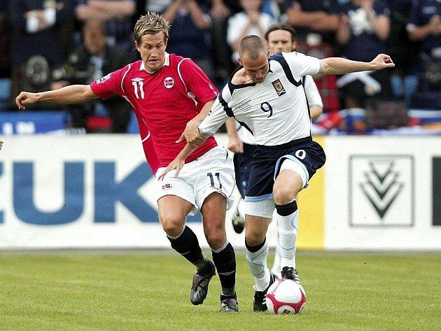 Nor Morten Gamst Pedersen (vlevo) bojuje o míč s Kenny Millerem ze Skotska.