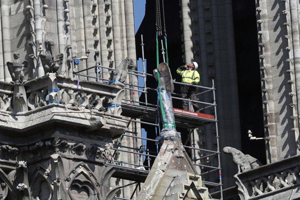 Poničená socha je připravena k transportu z katedrály Notre-Dame.