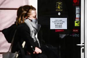 Žena s rouškou na obličeji 24. března 2020 prochází kolem zavřeného obchodu v pražských Vršovicích