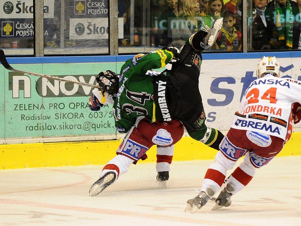 Útočník Karlových Varů Skuhravý padá po zákroku hostujícího hráče.
