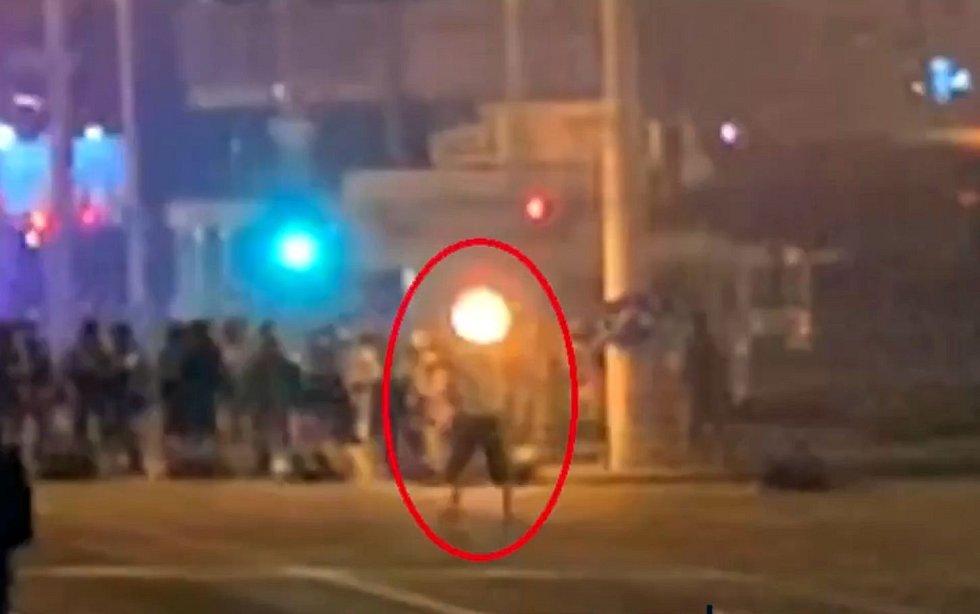 Záznam z pouličních kamer, zachycující smrt demonstranta Alexandra Tarajkovského (označeného červeným kroužkem). Na záznamu se objevuje výrazný záblesk, označovaný odpůrci oficiální verze za výstřel