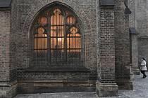 Žena prochází ve večerních hodinách kolem farního kostela sv. Prokopa na pražském Žižkově, 11. dubna 2020. Kvůli zákazu shromažďování kvůli koronaviru letos věřící nemohou chodit společně do kostelů a účastnit se obřadů. Křesťané si na Bílou sobotu připom