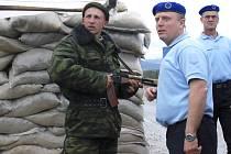 Členové unijní evropské pozorovatelské mise hovoří s ruským vojákem na kontrolním stanovišti u gruzínské vesnice Nabachtevi.