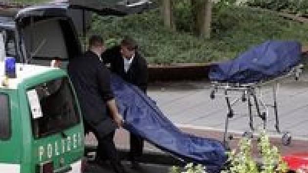 Policisté vynášejí mrtvá těla z místa tragédie.