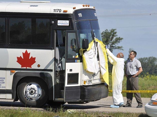Policisté zakrývají čelní sklo autobusu, v němž byla cestujícímu uřezána hlava.