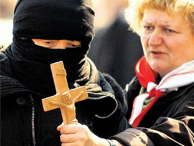 Potraty ne! Aktivistka proti potratům nastavuje kříž demonstrantovi, který ve Varšavě přišel na dubnové shromáždění za právo na žen jít na interrupci. Spory mezi přívrženci a odpůrci potratů otřásají Polskem už léta.
