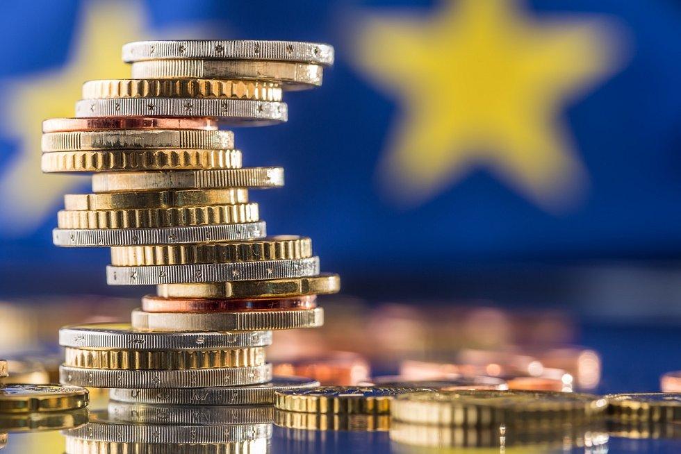 Věž s euromincemi a vlajkou Evropské unie v pozadí.