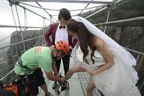 Novomanželé si ke stavbě zvolili čínský svátek zamilovaných, který připadá na devátého srpna. A přesto, že se houpali 180 metrů nad zemí, pořád se dokázali usmívat do objektivu na svatební fotografie.