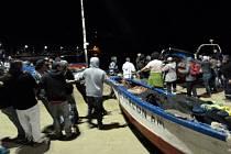 Lidé vytahují čluny z vody, snaží se je zachránit před vlnou cunami.