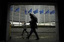Chodci během deštivého počasí v Bruselu míjejí sídlo Evropské unie na snímku z 16. října 2019