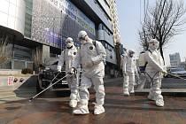 Pracovníci v ochranných oděvech dezinfikují prostor před kostelem v jihokorejském Tegu 20. února 2020
