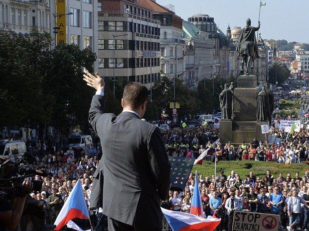"""Demonstrace """"Za naši kulturu a bezpečnou zem"""" se konala v Praze. Její pořadatelé jsou proti přijímání imigrantů a za vystoupení ČR z EU. Na snímku je poslanec Tomio Okamura při projevu (zády). Snímek z 12. září 2015."""