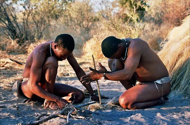 Křováci z botswanského údolí Deception Valley předvádějí rozdělávání ohně třecími dřívky