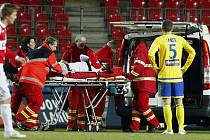Hráče Slavie Risteho Naumova nakládají zdravotníci do sanitky poté, co utrpěl otevřenou zlomeninu dolní končetiny.
