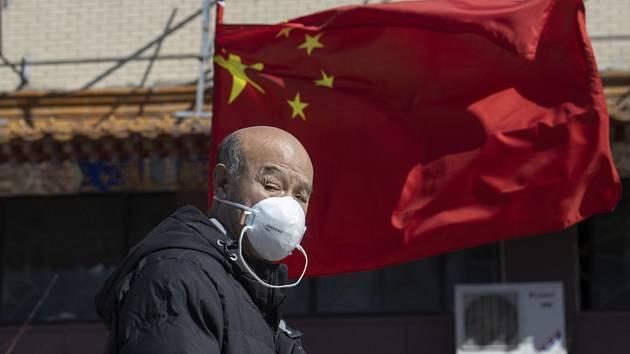 Muž s rouškou u nemocnice v Pekingu.