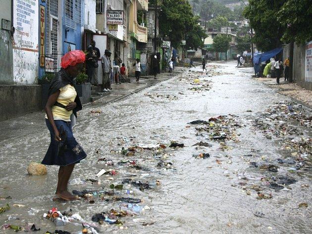 Nejničivější bouře letošní sezóny v Karibiku dostala jméno Gustav a do pátečního poledne zabila už 67 lidí, Žena utíká ulicí zasažené povodní, kterou vyvolal hurikán Gustav.