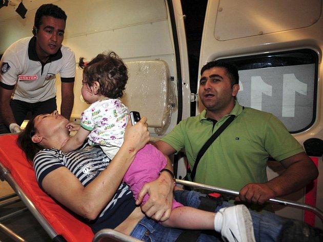 Žena zraněná při nedělním pumovém atentátu v centru Istanbulu je odvážena se svým dítětem do nemocnice. Útok si vyžádal nejméně 16 mrtvých a přes 150 zraněných.