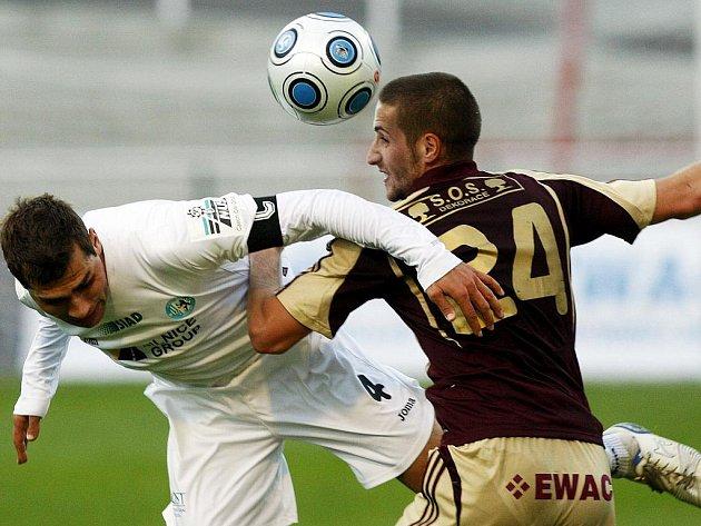 O míč bojují Petr Malý z Dukly ( v červeném) a Martin Knakal z Mostu.