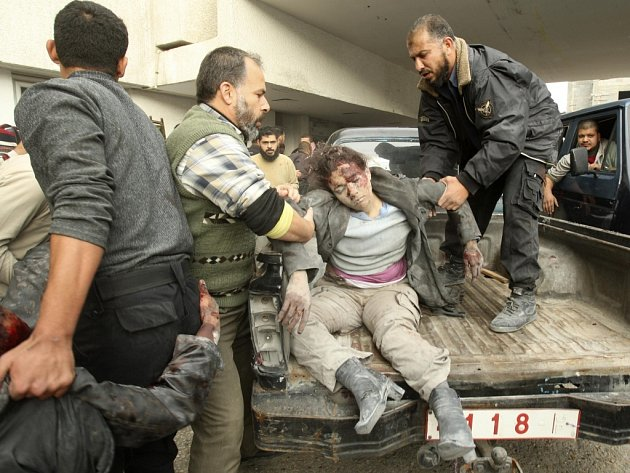 Palestinci nakládají na vozidlo ženu, zraněnou při izraelském náletu na město Gaza.