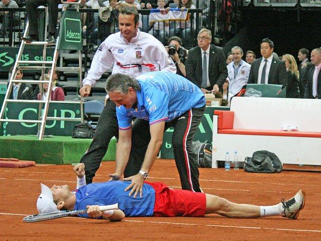 Tomáš Berdych leží na dvorci po vítězství nad Srbskem. Gratulují mu kapitán Jaroslav Navrátil (vpravo) a Radek Štěpánek.