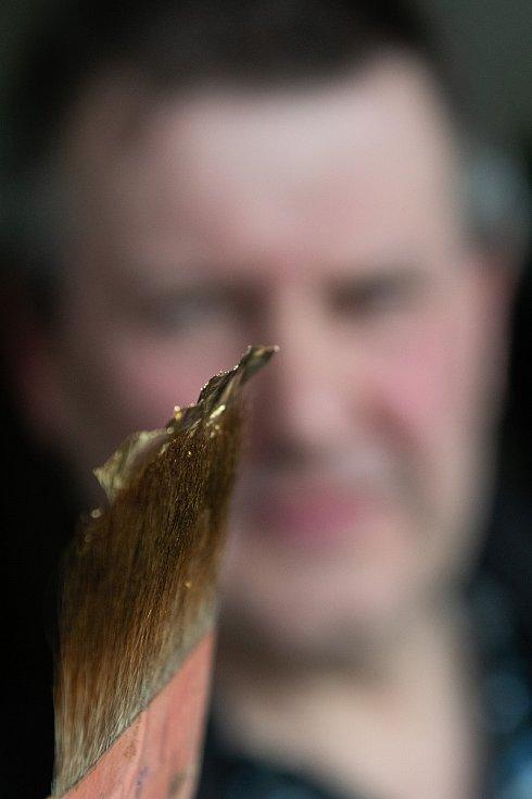 Zlaté plátky jsou tak tenké, že při práci Václav Hodinka skoro ani nedýchá. Plátky přichytí pomocí vazelíny na z štětec z veverčích chlupů.