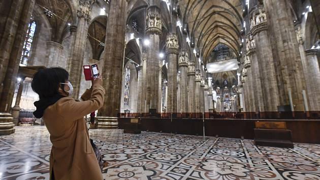Turista s rouškou fotí interiér gotické katedrály Narození Panny Marie v Miláně (italsky Duomo di Milano)