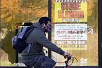 Muž s rouškou projíždí na kole kolem zavřeného obchodu ve městě Wilmette v americkém státě Illinois.