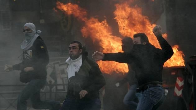 Protestující mladíci vrhají kameny na policisty v Aténách.