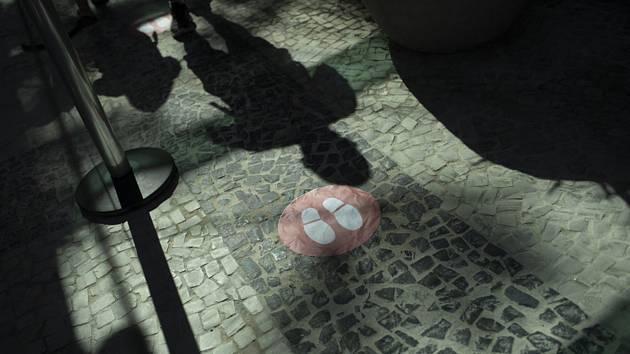 Stíny zákazníků, kteří vstupují 11. června 2020 do obchodu, se odrážejí na dlažbě v Riu de Janeiro
