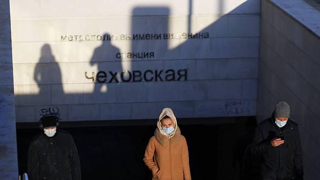 Lidé v rouškách na shodišti stanice metra  Čechovskaja v Moskvě.