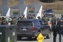 Střelec na severu kanadské provincie Nové Skotsko zabil během 12 hodin nejméně 16 lidí, včetně policistky. Na snímku policisté na čerpací stanici v Enfieldu zaujímají pozice při zatýkání muže, který byl podezřelý ze střelby.