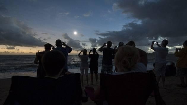 Lidé na pobřeží Austrálie sledují zatmění slunce