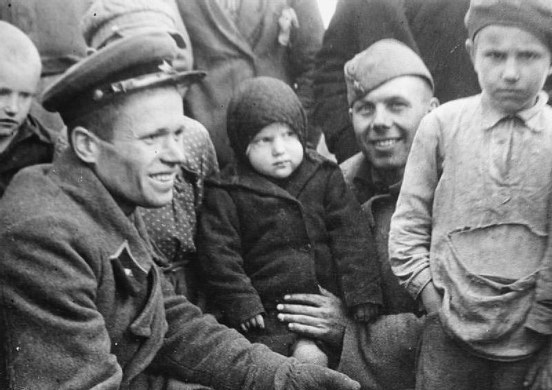 Poručík Y. Krivošejev Rudé armády a jeden z jeho vojáků, kteří se pokoušejí navázat přátelství s viditelně nespokojenými místními dětmi ve vesnici Kevly v Sověty okupované části Polska